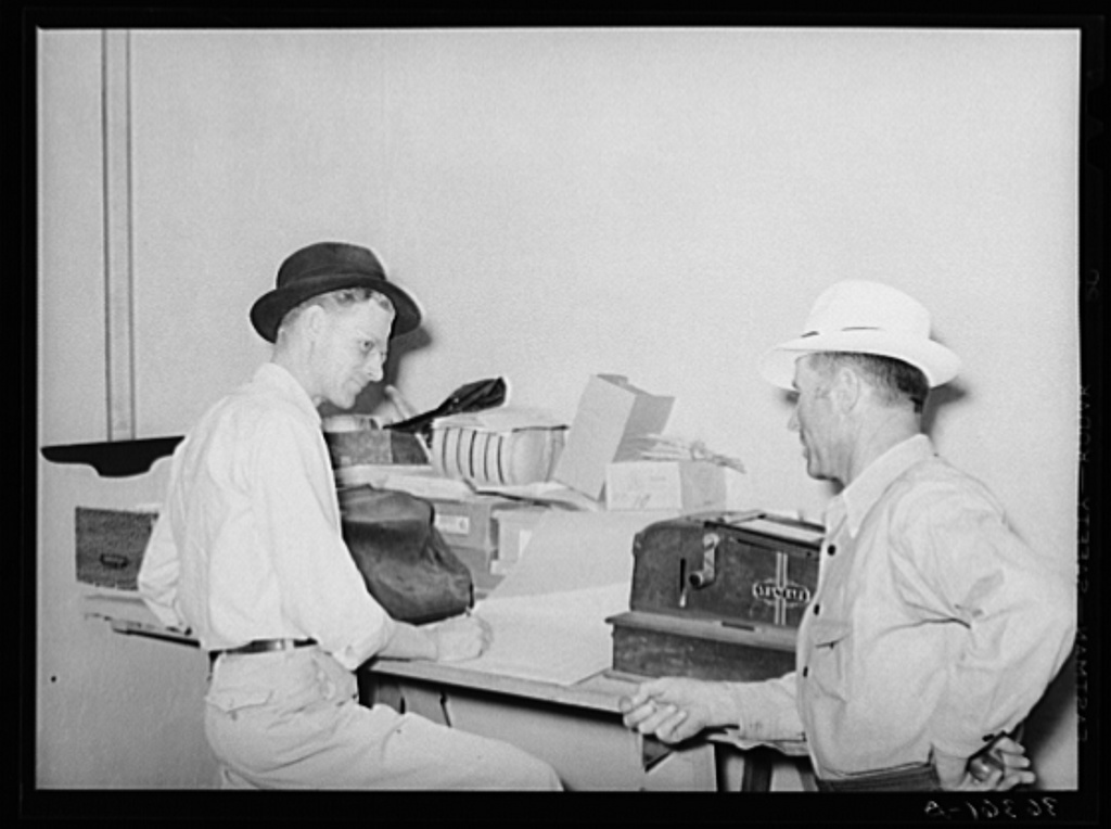 Assistant manager of the Casa Grande Valley Farms, Pinal County, Arizona, discussing a report with a member of the cooperative