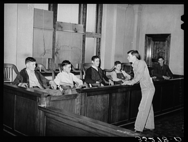 """At county 4-H Club meeting members from one community put on a one act play in which Farmer Brown was tried and indicted for """"cruelty to his farm."""" His neighbors testified to his spurning of soil conservation practices, etc. District attorney is shown charging the jury. Eufaula, Oklahoma"""