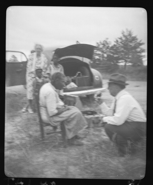 """[Aunt Harriett McClintock at the microphone with John A. Lomax, Sr., Mrs. Ruby Pickens Tartt, and Aunt Harriett's """"great-grands"""" children in background, at crossroads near Sumterville, Alabama]"""