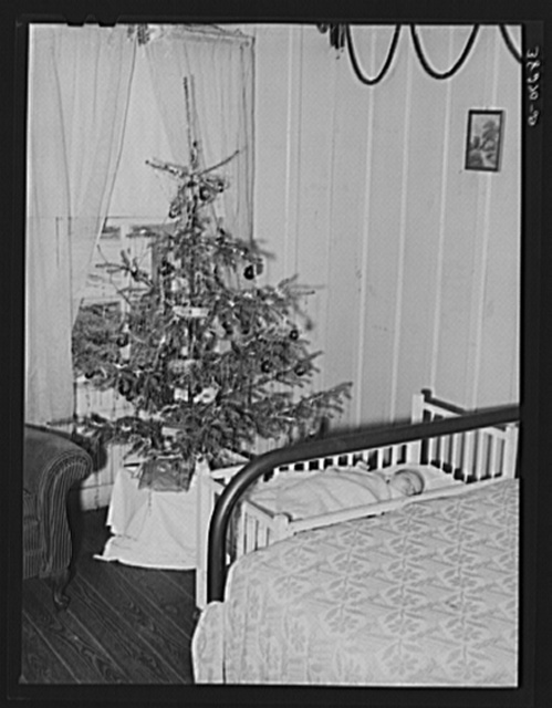 Baby and Christmas tree in corner of living room in home of construction workman. This family came to Corpus Christi from northwest Texas eight months ago