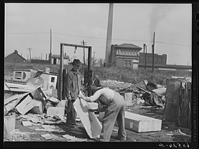 Baling papers and cardboard boxes salvaged from the city dump. Dubuque, Iowa. These men live in shacks just on the edge of the dump. Their entire income is derived from what they can pick up in their daily rounds of the dump
