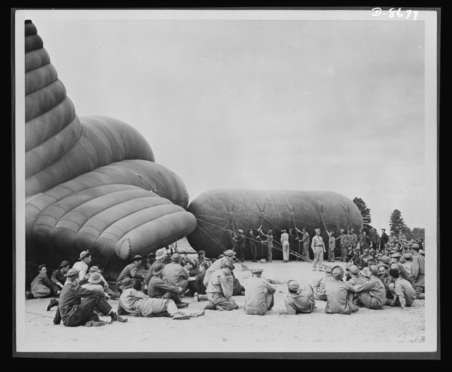 Balloon barrage training center. Lilluputians at a weemie roast. This illustration is portrayed here by comparing the huge balloons and dwarfed trainees seated in picnic fashion around their instructor. Camp Tyson, Tennessee