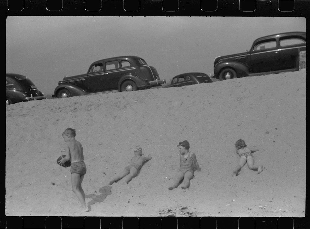 """Beach scene at """"New Beach,"""" the most popular beach near Provincetown. Regular bus service makes this beach easily available; lack of bath houses causes a great deal of picturesque dressing and undressing in and behind parked cars. Provincetown, Massachusetts"""