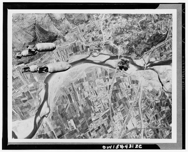 Bombs hurtle toward a Nazi highway bridge. With their rail and shipping facilities almost completely disrupted, the Germans were forced to resort to motor transport. All roads and bridges in central Italy became targets for Allied aerial assaults