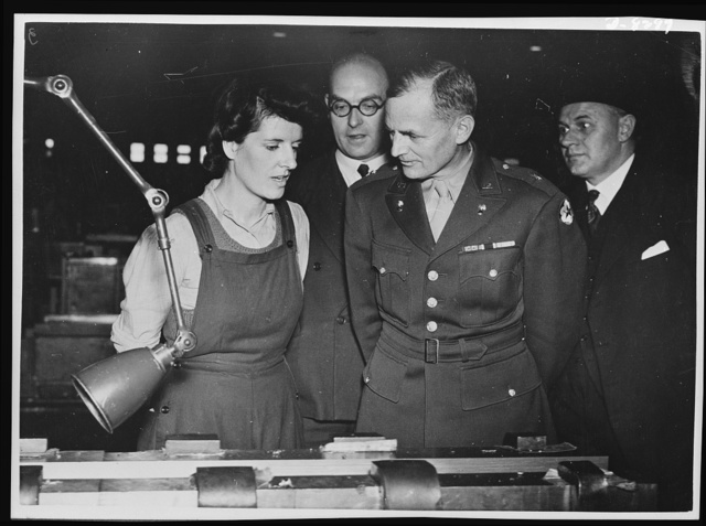 Brigadier General Barnes. Brigadier General Barnes, Assistant Chief of Ordnance, U.S. Army, and head of the Design Division of the U.S. War Department, is now touring Ministry of Suply munition factories. General Barnes talking to Mrs. Martha Haddon, now working in a gun factory, and formerly a housewife. On General Barnes' left is Mr. H.E. Harris, the Deputy Director General of Ordnance Factories. In between the General and Mr. Haddon, is the factory superintendent