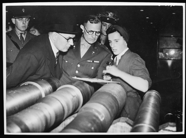 Brigadier General Barnes. Brigadier General Barnes, Assistant Chief of Ordnance U.S. Army, and head of the Design Division of the U.S. War Department is now touring Ministry of Supply Munition Factories. General Barnes taking keen interest in the work of Miss Joan Leanoy, who is gauging 25 pdr. gun barrels