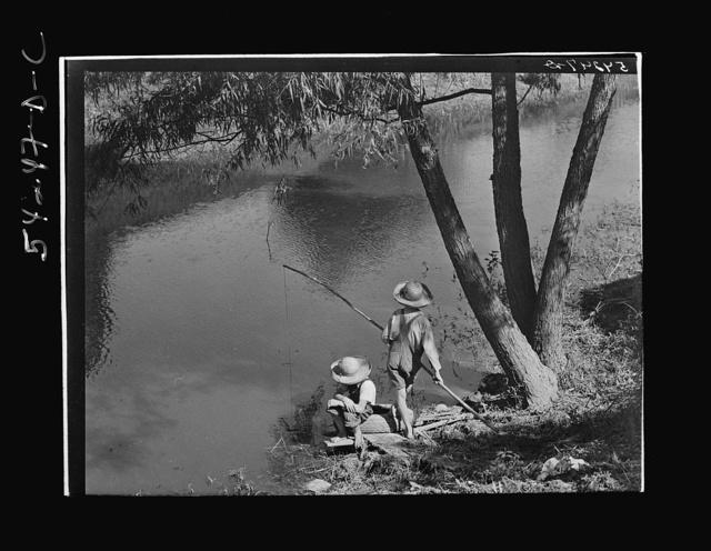 Cajun children fishing in a bayou near the school by Terrebonne Project. Schriever, Louisiana