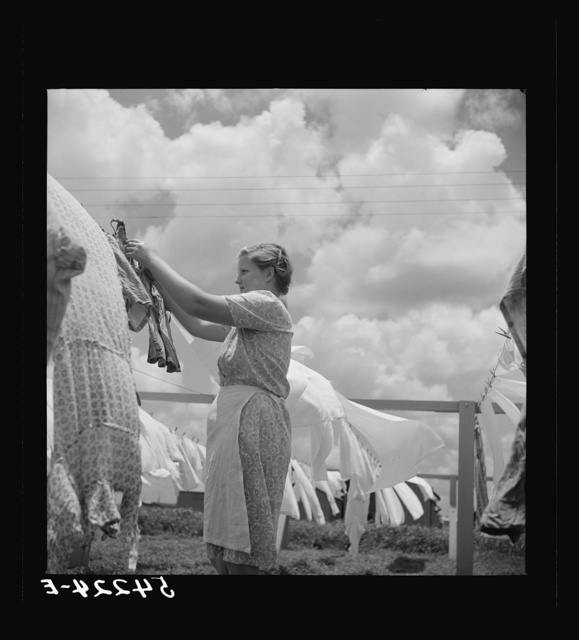 Camp member hanging out clothes outside of utility building which is equipped with complete laundry facilities and showers. Osceola migratory camp, Belle Glade, Florida