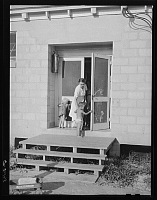 Camp member taking her child into utility building for a shower. Osceola migratory labor camp. Belle Glade, Flordia