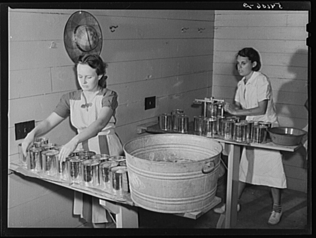 Camp members canning tomatoes in the utility building at Osceola migratory labor camp. Belle Glade, Florida