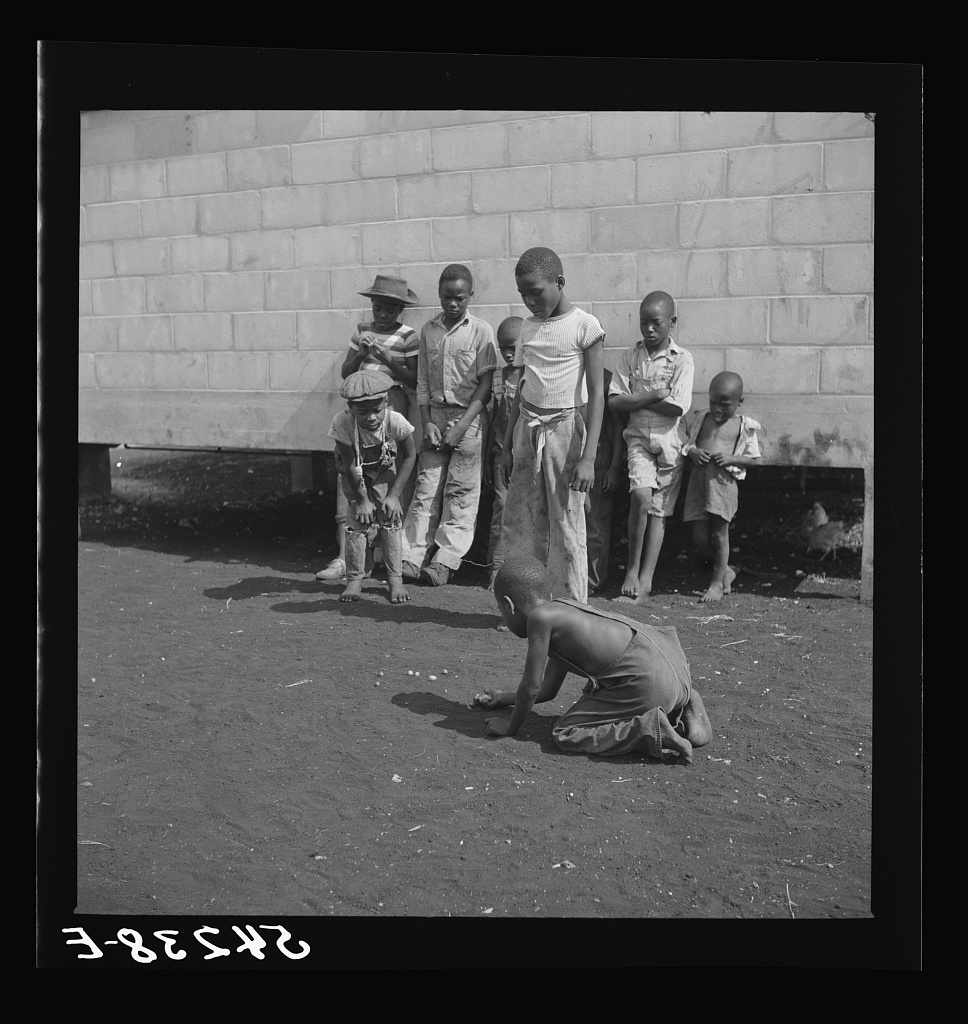 Camp members' children playing marbles outside their shelter
