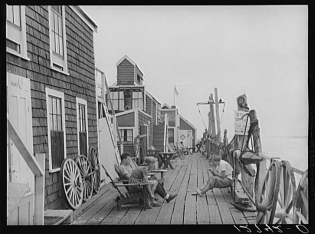 "Captain Jack's Wharf, formerly a fish pier, now a tourist colony mainly inhabited by ""artists."" Previously the shacks had been used for storing and repairing of nets and gear. Provincetown, Massachusetts"