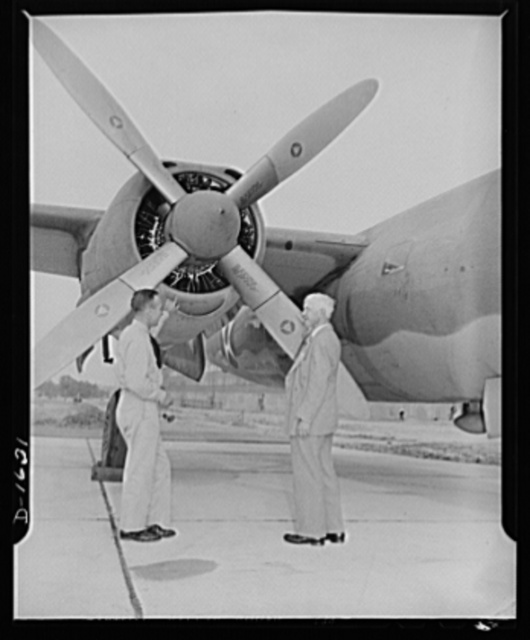 "Carl Sandburg, author of the commentary to the Office of Emergency Management (OEM) motion picture, ""Bomber"" discuuses some of the finer points of the construction of the Glenn L. Martin bomber with chief production test pilot, Roland Lee Sansbury"