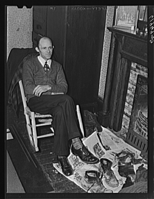 Carpenter at Hercules powder plant in his room in Sunday clothes, workclothes on the floor in front of him. He came here a month ago from Long Branch, West Virginia. Pays eight dollars a week room and board. Left his family at home. Would send for them if he could find a decent place to live. Radford, Virginia