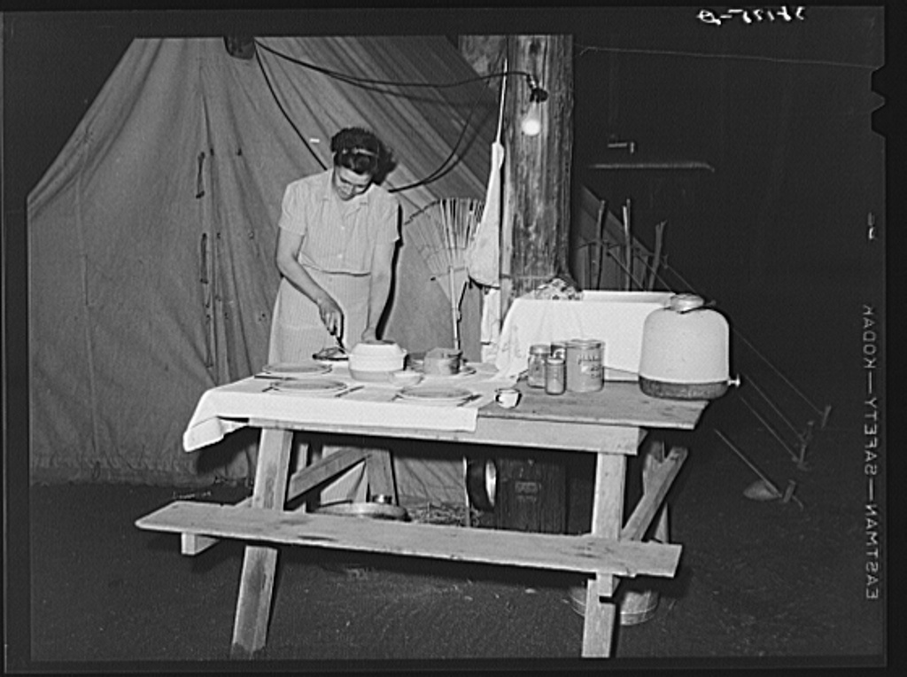 """Carpenter's wife setting the table in front of their tent home. Mission Valley, California, which is about three miles from San Diego. These people followed construction work in Texas, Louisiana, Illinois and Arizona. They have never lived in a tent before but the man said, """"I know this work-spree isn't going to last and I'm not giving all I make to the landlords."""""""