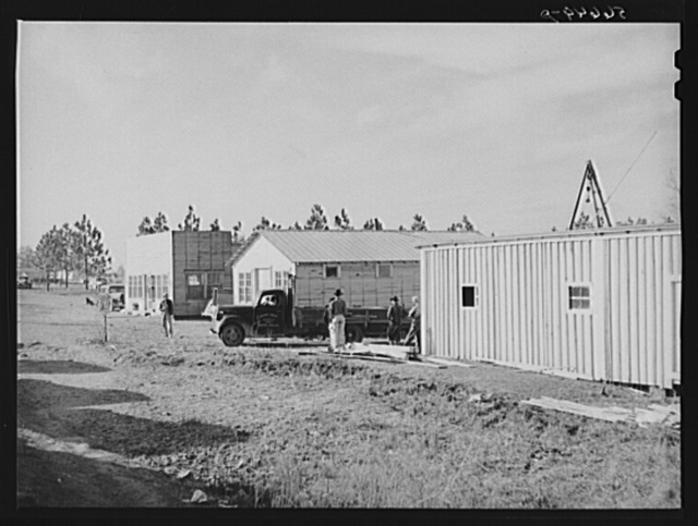 Cars of construction workers at Camp Claiborne, Alexandria, Louisiana. New buildings on highway at Camp Claiborne. Cabins, sleeping quarters, etc., being built by private interest for construction workers. Louisiana