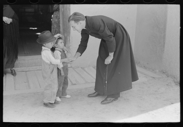 Catholic priest greeting small Spanish-American boy after Mass. Trampas, New Mexico