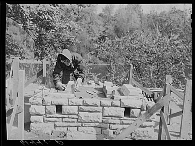 CCC (Civilian Conservation Corps) boy building charcoal burner at picnic grounds of recreation area. Ross County, Ohio