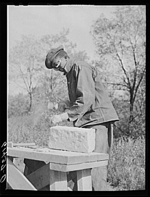 CCC (Civilian Conservation Corps) boy chopping stone for use in building charcoal burners at picnic grounds. Ross County, Ohio, recreation area