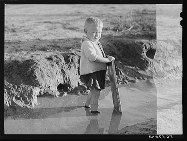 Child playing in front of his home on Milstead Avenue about five miles outside of Columbus, Georgia. Near Fort Benning. His father is at Fort Benning