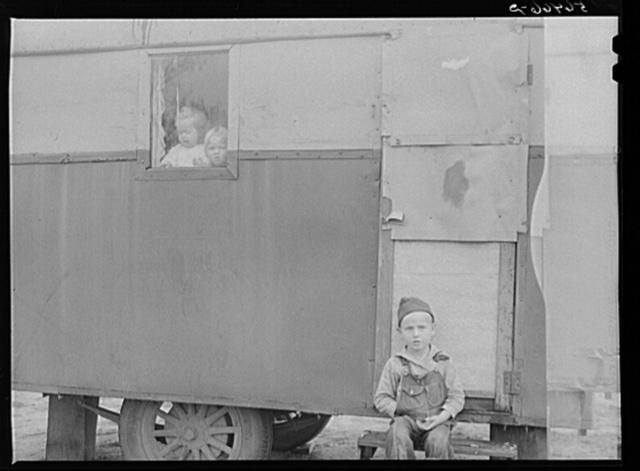Children looking out of trailer window. Trailer where C.E. Childre and family live in highway about three miles from Fort Benning. He is an auto mechanic and came up to Columbus, Georgia two weeks ago from Albany, Georgia and now works at Columbus Motor Company. They couldn't find any other place to live so had to get a trailer. They pay two dollars a week for space in W.T. Mullis' backyard. Never lived in a trailer before, don't like it, difficult with children and wet weather