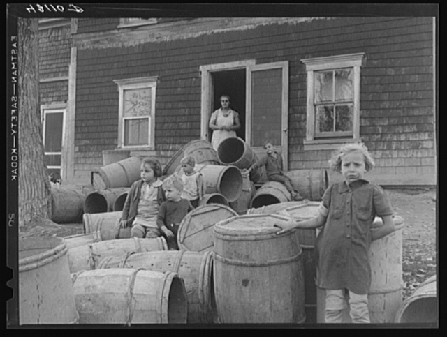Children of Baptiste Deprui, French-Canadian potato farmer. He runs a small seed foundation unit and also raises some certified seed oats. The barrels in front of the house were left there after he had stored all the potatoes in the cellar of the house. The potatoes completely filled the cellar as high as the floor boards. Soldier Pond, Maine