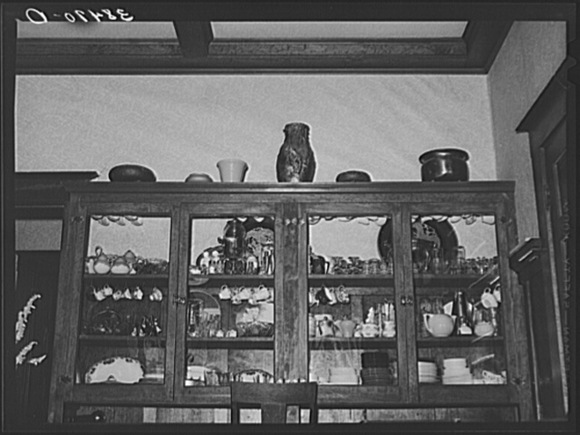 China cabinet in home of fruit farmer. Placer County, California. These fruit specialists have had a high standard of living, are now losing their farms