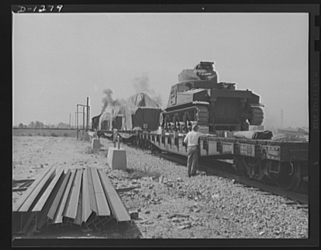 Chrysler tank arsenal. A trainload of complete M-3 tanks roll away from the huge Detroit Chrysler tank arsenal, to be delivered to the Army. Each of these tanks weigh over twenty-eight tons. The camera shows only the rear of the tank in the foreground. Note the 150 calibre machine gun. Three other machine guns, a 75mm. gun and a 37mm. anti-aircraft gun are also mounted on the steel giant