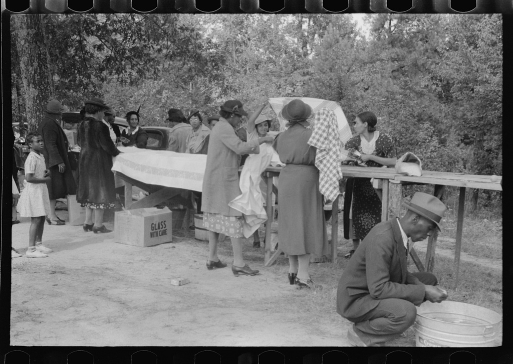 Cleaning up and visiting after outdoor picnic at an all-day ministers and deacons meeting. Near Yanceyville, Caswell County, North Carolina