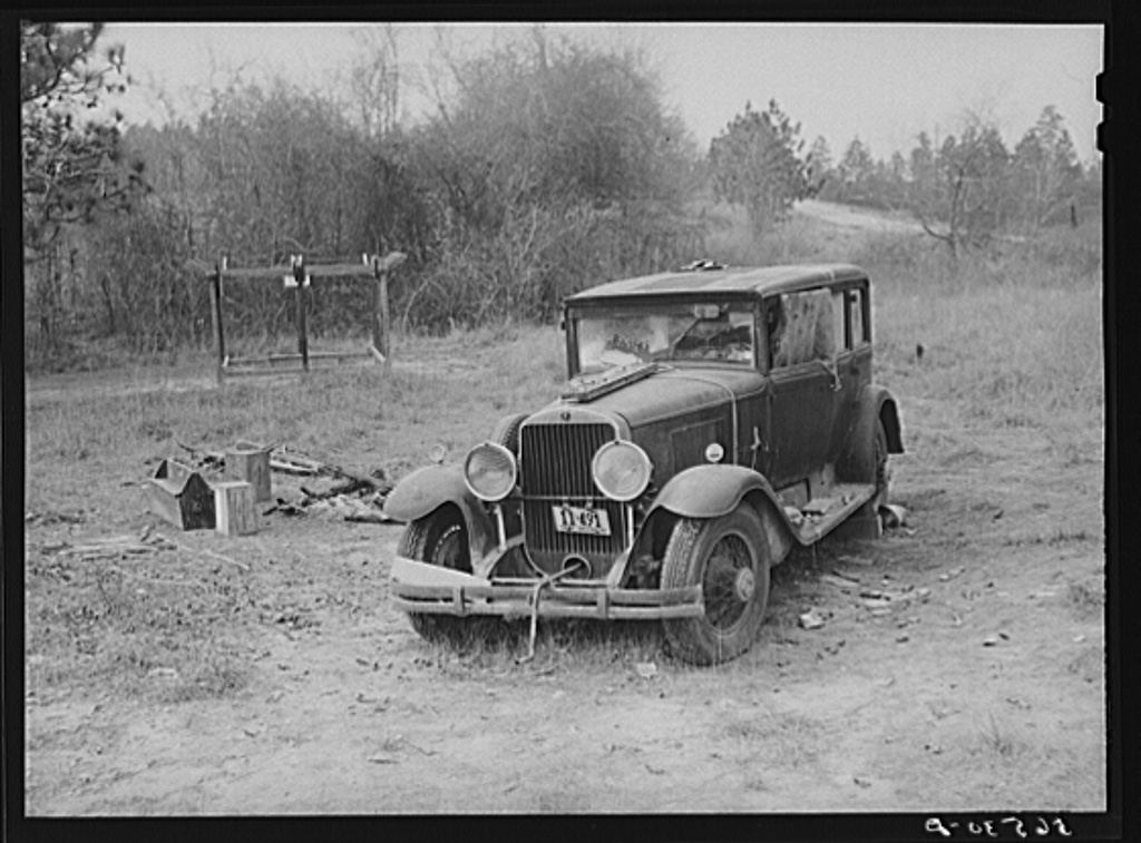 Close-up of car from Mississippi used for sleeping as well as shelter and traveling. Evidences of cooking outdoors are beside it. On highway near Camp Livingston, Alexandria, Louisiana