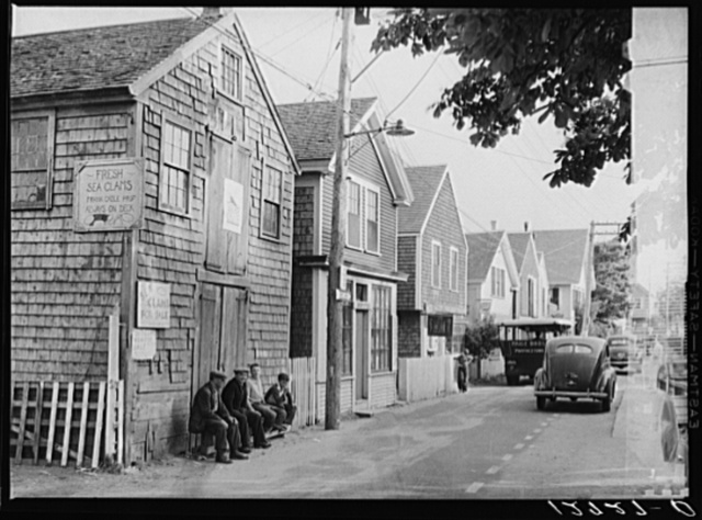 """Commercial Street, the main street of Provincetown which runs along the waterfront, including a view of the """"Sand Bar Club"""" and the tourist bus which runs out to the beach. Provincetown, Massachusetts"""