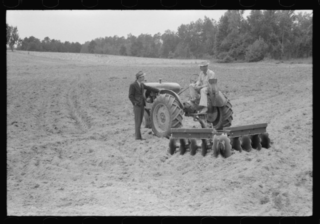 Connie B. Gay, FSA (Farm Security Administration) county supervisor talking to Emery Hooper about his tractor and disc plow purchased with a FSA cooperative community service loan. Near Prospect Hill, Caswell County, North Carolina