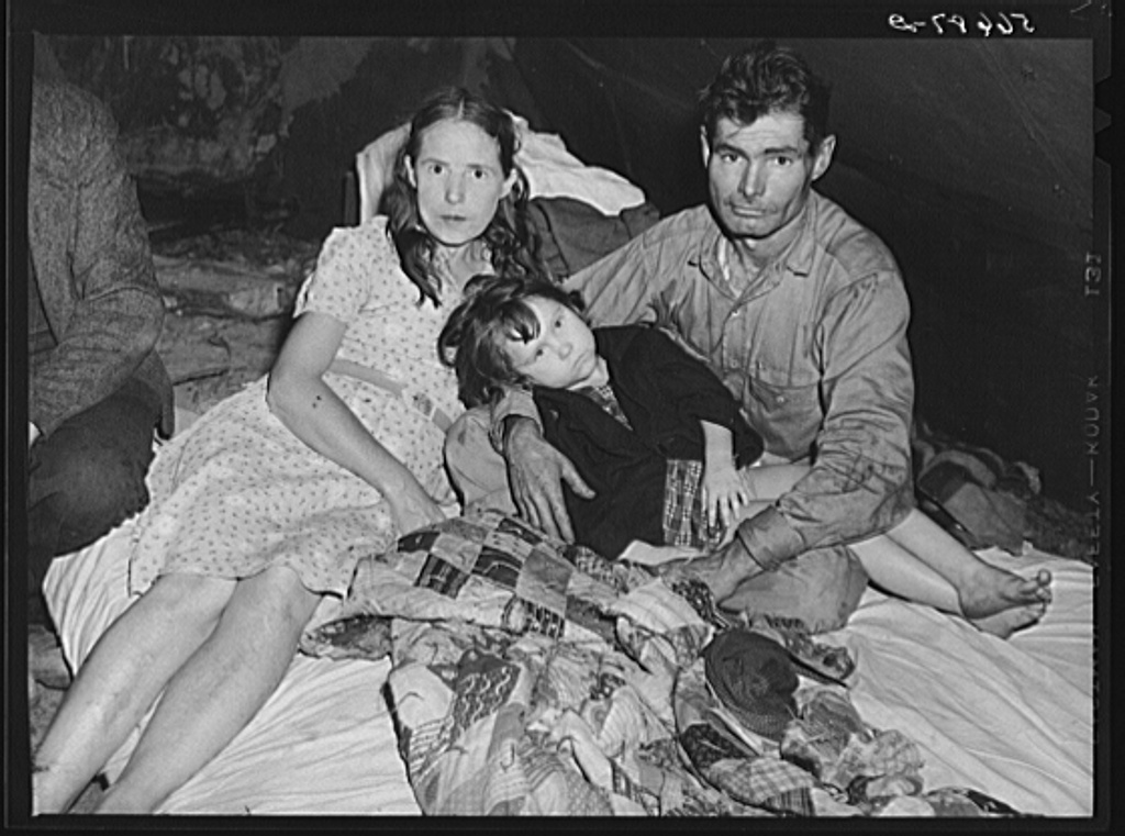 Construction worker with wife and neighbor's child in tent home near Alexandria, Louisiana. Ten men, two women, and two children live here