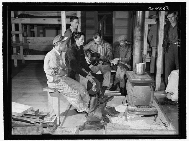 Construction workers around stove after work in new craftsmen's barracks. Camp Blanding, Florida