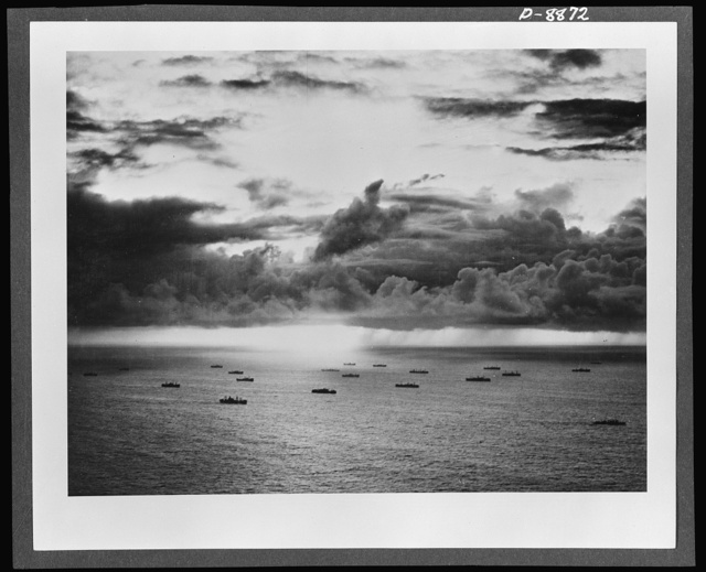 "Convoy. Silhouetted against a tropical sky, an American convoy plods steadily across the broad Pacific. Ships like these and the naval vessels and planes that protect them are maintaining the ""bridges of boats"" that link us with our far-flung battle fronts"