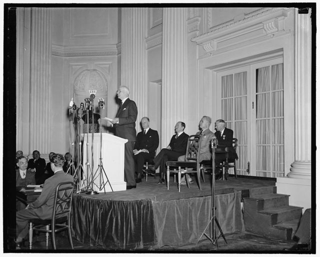 [Cordell Hull at podium; Sumner Welles and others on platform]