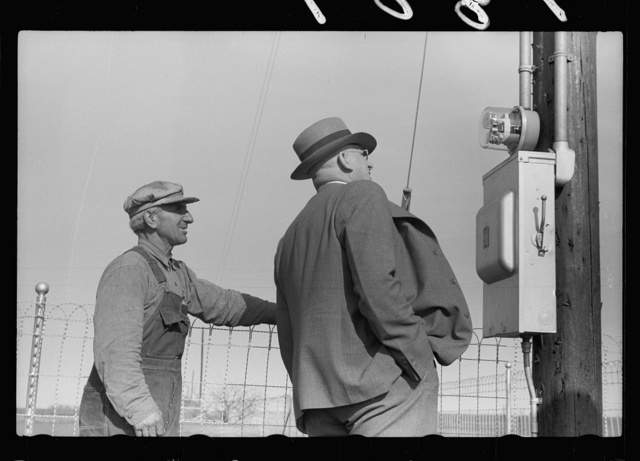 County agent and farmer looking at electric meter on farm, Grundy County, Iowa