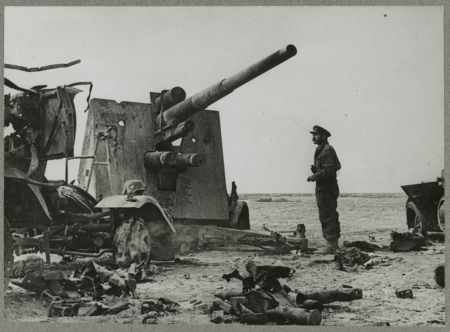 Cyrenaica reconquered - An eighth Army officer beside a German dual purpose 88 mill. gun, put out of action by British Artillery near El Gubbi. This gun is used both for anti-aircraft and long range shelling