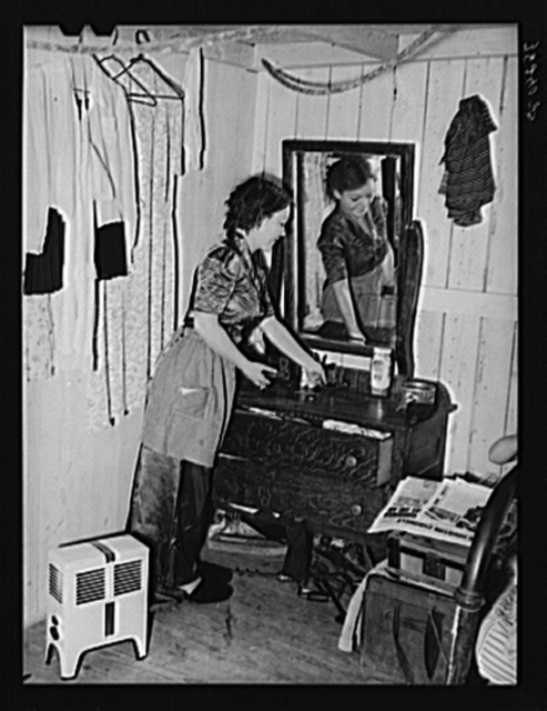 Daughter of carpenter from Hobbs, New Mexico, straightening dresser in room in tourist court which is now the family home