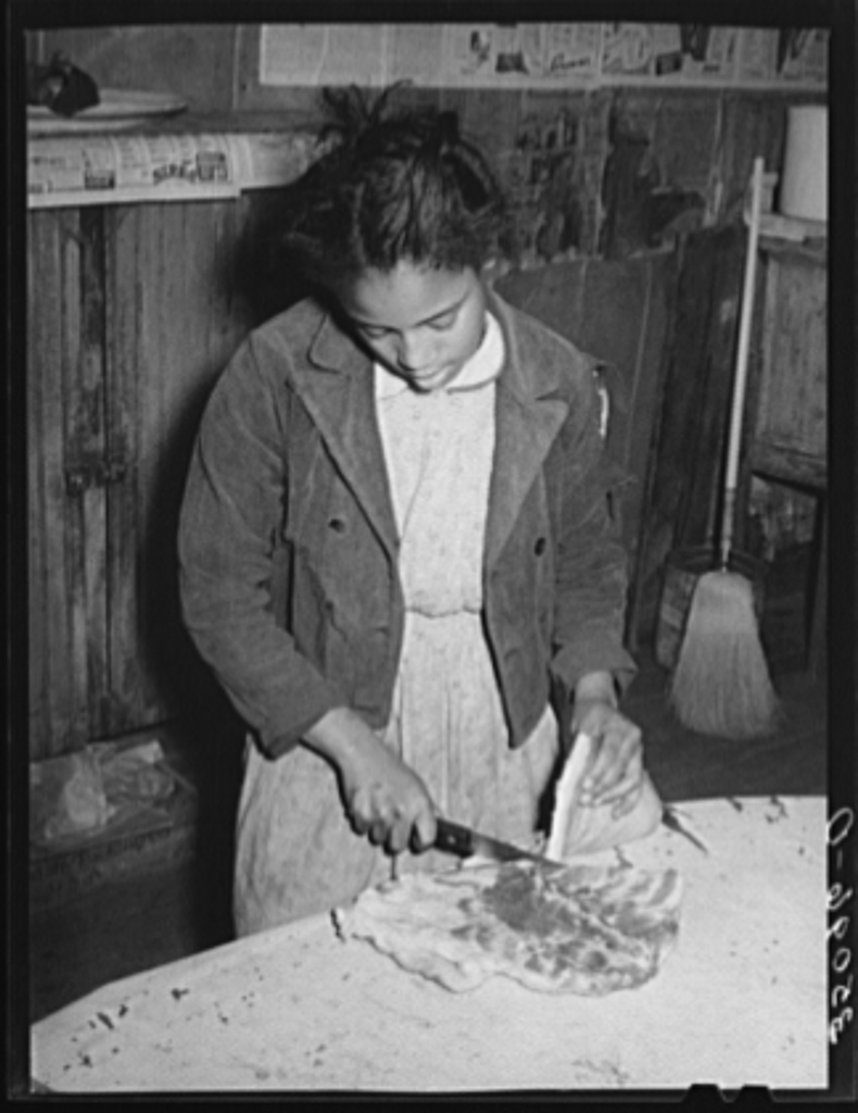 Daughter of Pomp Hall, Negro tenant farmer, slicing bacon. Creek County, Oklahoma. See general caption number 23