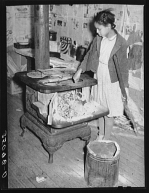 Daughter of Pomp Hall, Negro tenant farmer, taking ashes out of stove before building fire in the morning. Creek County, Oklahoma. See general caption number 23