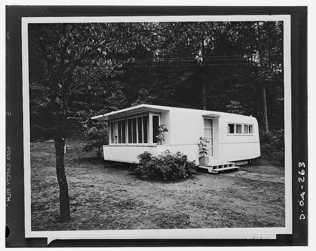 Defense housing. The completely assembled trailer house. Last steps in the assembly were the attaching of the steps and the entrance canopy. The Tenessee Valley Authority (TVA) is experimenting with two types of exteriors. One, shown in the picture, embodies the customary streamline of a trailer. The other follows as closely as possible the