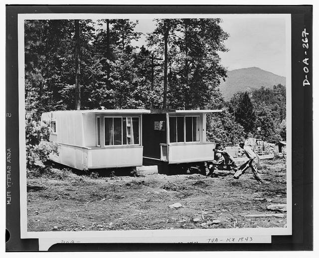 Defense housing. The second section of the experimental trailer-house is joined to the first section. The workmen will have the house ready for occupancy in something like half a day from the time they started its assembly. The house will then be occupied by a worker at the Tennesse Valley Authority's (TVA) Fontana project, which is being