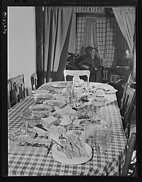 Dinner table after dinner at Mrs. Jones's boardinghouse. Sixteen men live here. Men in background sitting in parlor after dinner. Radford, Virginia