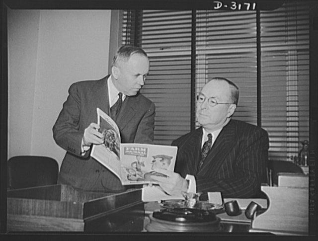 """Donald Nelson, Chairman of the War Production Board, studies the program by which America's farm women plan to help win the war. Graham Patterson, publisher of Farm journal and farmer's wife, national farm magazine, is seen here presenting the """"War Platform"""" which twenty-eight leading farm women, speaking for the rural homemakers of America, drew up in a recent Chicago conference sponsored by this magazine. Several sections of the platform were addressed directly to Mr. Nelson's board and other goverment agencies. It contains thirty-one practical ways in which farm women declare they can help"""