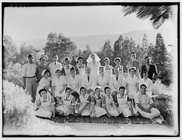 Dr. H. Torrance, Tiberias. Group. Staff with sea in background