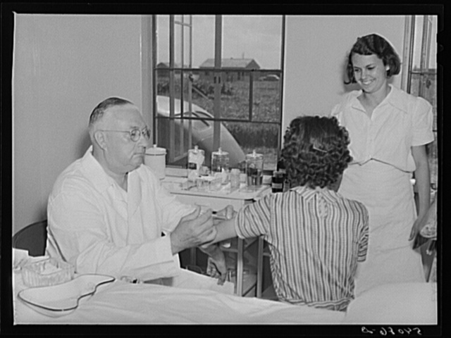 Dr. William J. Buck gives typhoid shot to one of camp members with Marjory Fowler, NYA (National Youth Administration) member assisting the nurse. Osceola migratory labor camp, Belle Glade, Florida