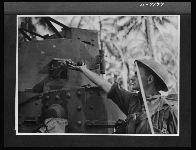 During the thick of the fighting at Buna, an Australian infantryman receives a handful of grenades from a fellow soldier inside the tank. American tanks manned by Australian crews, carried large quantities of grenades which were distributed to the infantry. This picture was made during the actual fighting