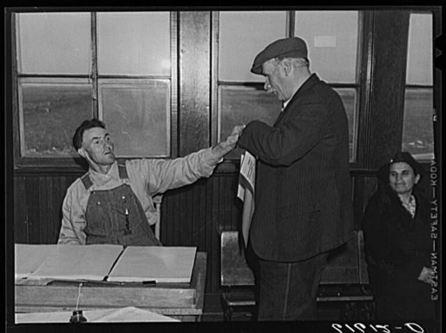 Election inspector handing ballot to farmer. Beaver Creek precinct, McIntosh County, North Dakota