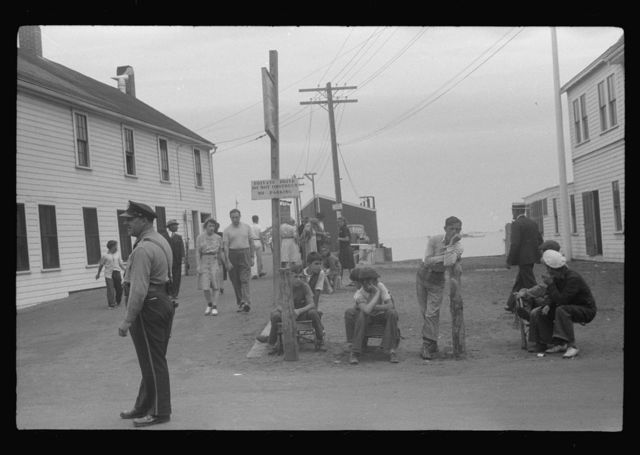 Entrance to the town pier before the arrival of the Boston boat. The policeman is an institution, knows everybody, even every summer visitor. The boys wait for the chance of carrying somebody's baggage. Provincetown, Massachusetts